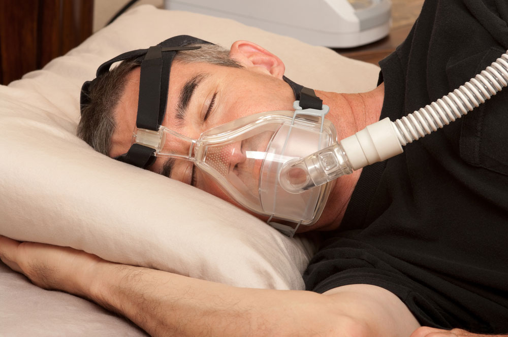 Man in black t-shirt sleeping with CPAP mask on his face for sleep apnea