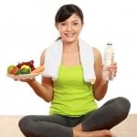 fit woman holding fruit and water