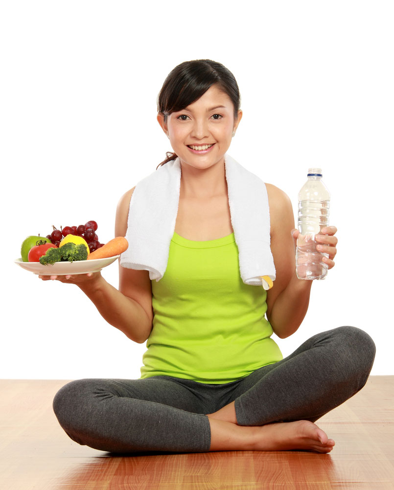 Woman sitting crossed legged in workout clothes holding plate of fruit and water bottle