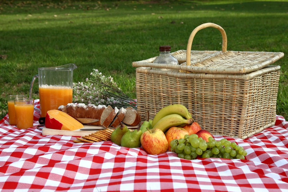 Picnic basket on red checked table cloth with fruits, cheese and juice drinks