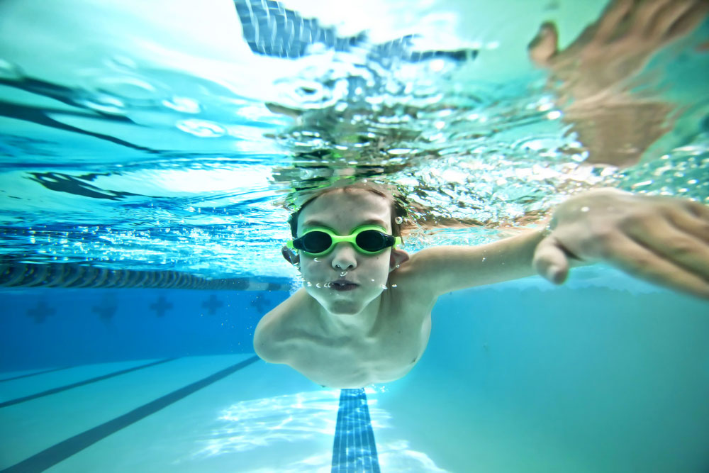 Young child swimming in pool with green goggles
