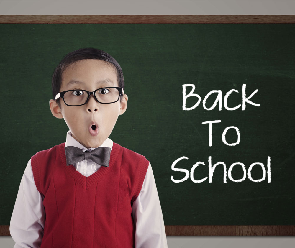 Young boy student in bow tie and red vest in front of chalkboard that says, 'Back To School'