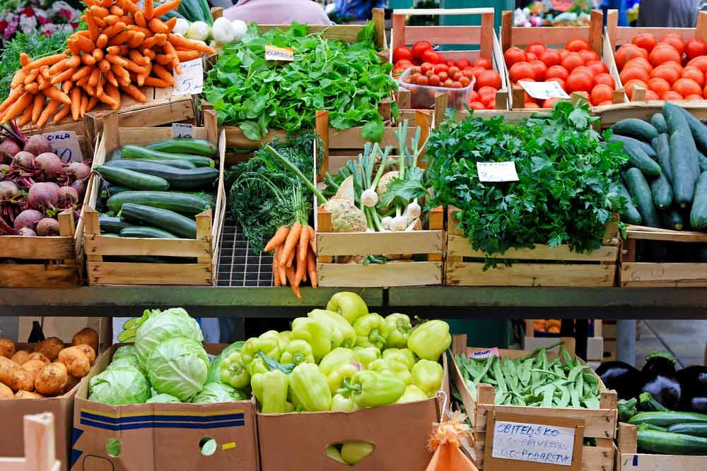 Farmers market crates of vegetables - carrots, lettuce, cucumbers