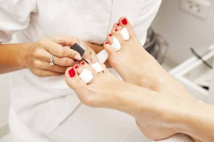 Woman's feet with red polish having a pedicure