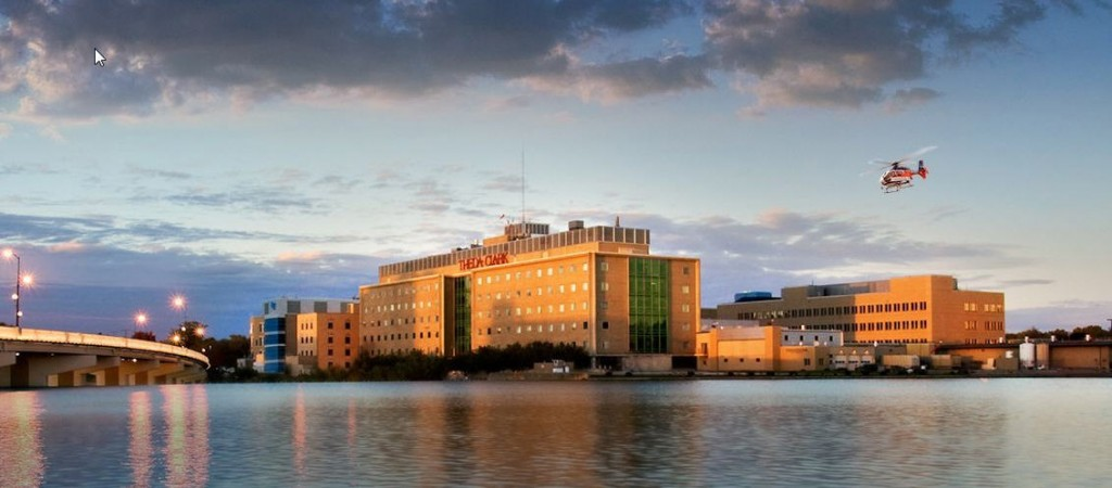 Wide shot of ThedaCare Medical Center in Neenah, Wisconsin with bridge on left and river in foreground
