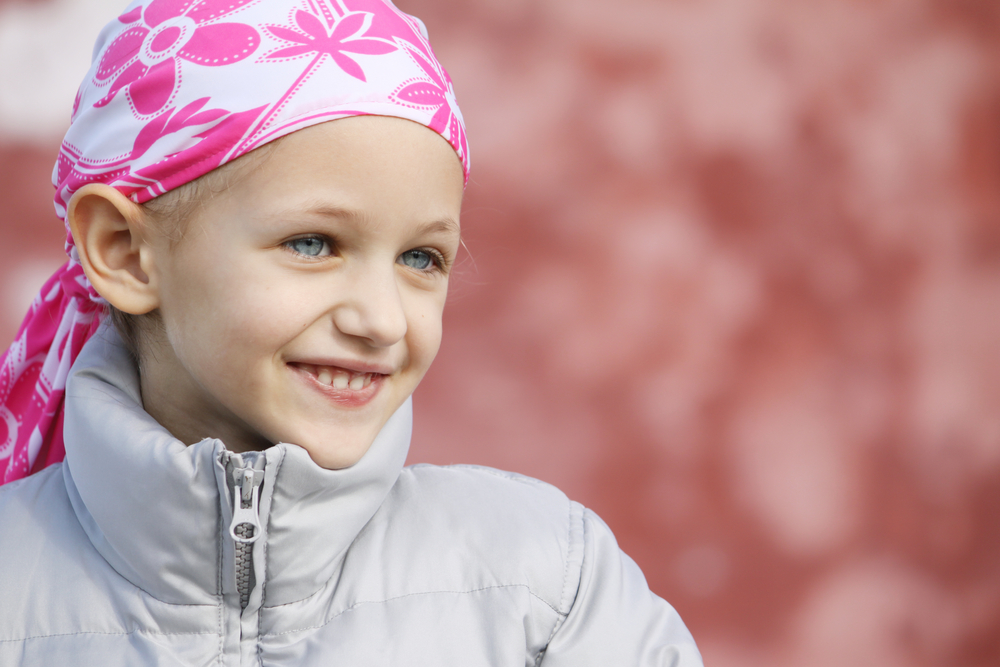 Young girl with pink and white bandana on her head after losing her hair to chemo treatment