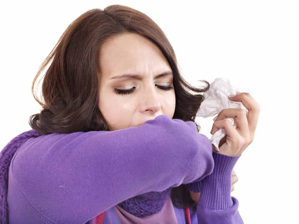 woman in purple sweater holding a kleenex coughing into her elbow