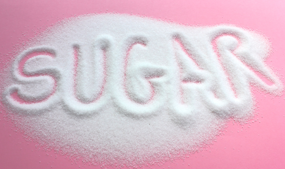 The word sugar written into a pile of white granulated sugar with a pink background
