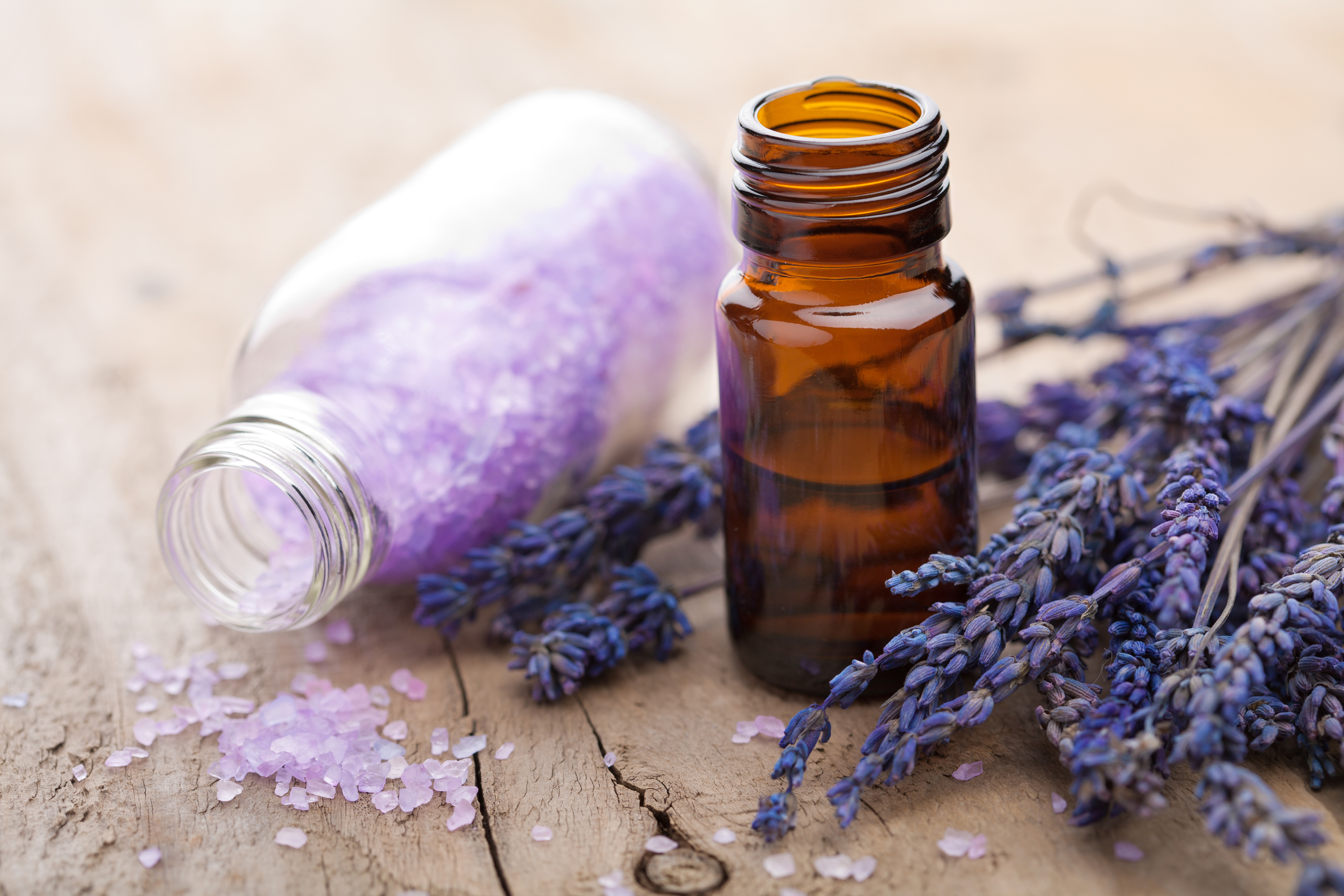 sprigs of purple lavendar with a small bottle of lavendar crystals and brown bottle of lavendar oil