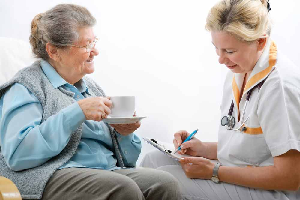 Senior woman holding tea cup and visiting with female doctor or nurse who is taking notes
