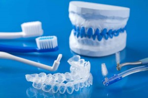 dentures, toothbrushes, tooth whitening trays, water pic on blue background