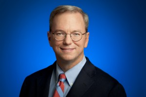 Medium shot of Eric Schmidt wearing glasses in dark suit and red striped tie with blue background