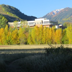 Wide shot of the Aspen Valley Hospital with fall leaves on trees and blue sky in the background
