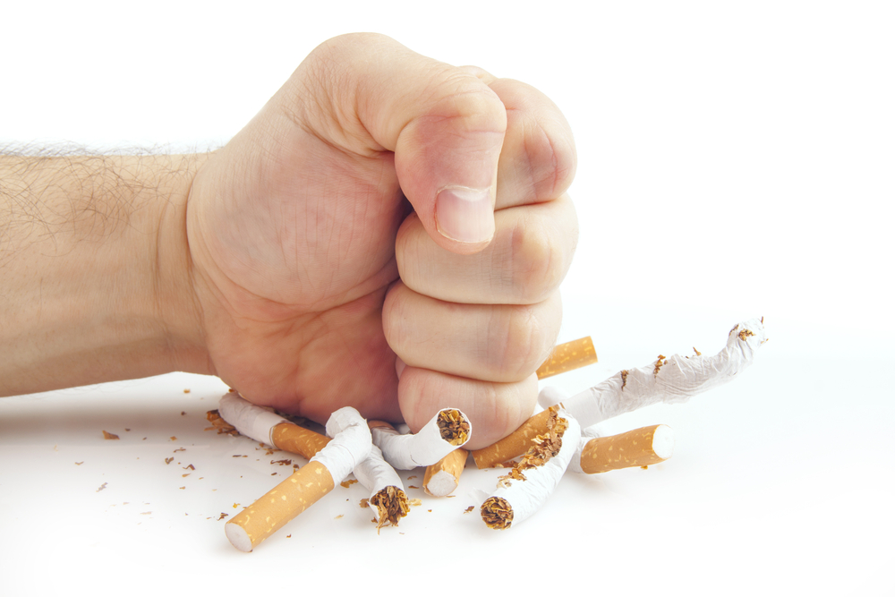 Caucasian man's fist pounding down on a pile of broken cigarettes