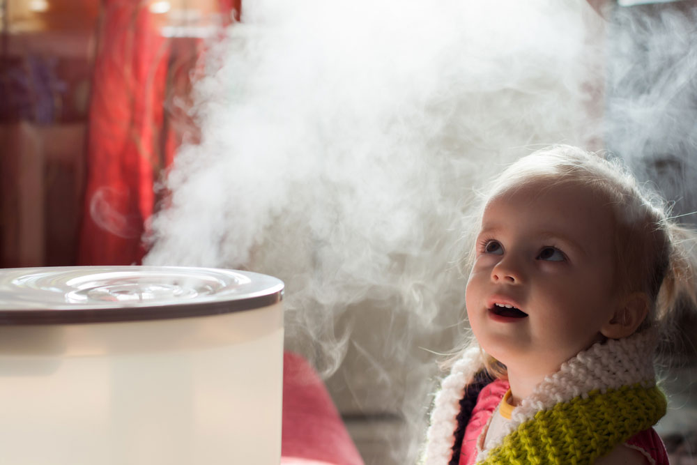 Young caucasian girl standing near humidifier with steam filling the room