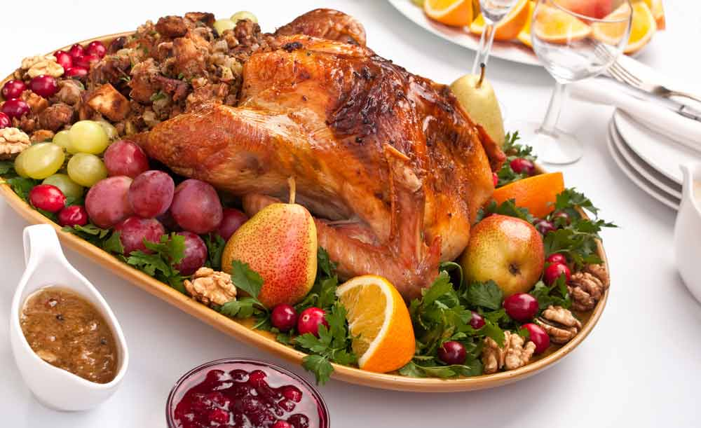 Roasted turkey on platter surrounded by fruit, nuts and vegetables on a white tablecloth