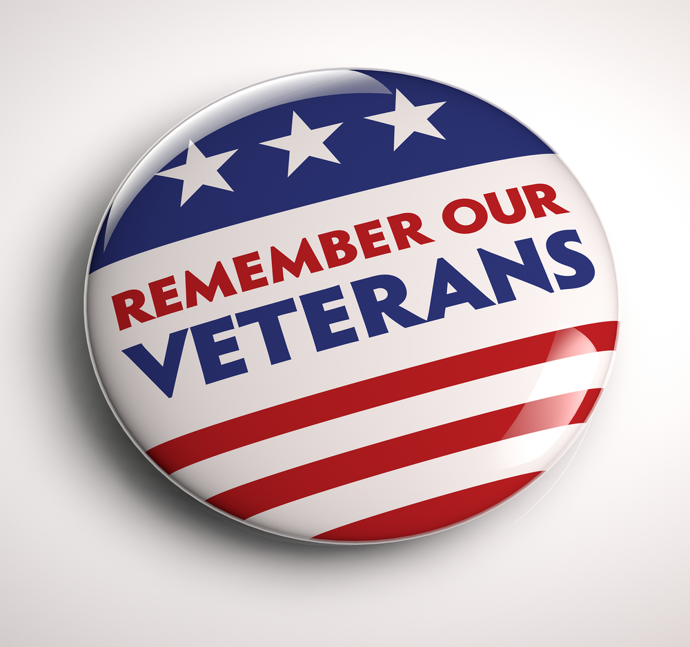 Red, white and blue button that says Remember Our Veterans