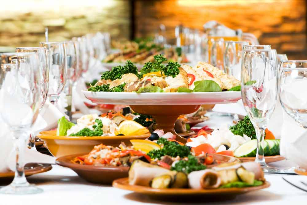 Large dining table with platters of healthy foods, mostly vegetable and fish, and clear glass champagne goblets
