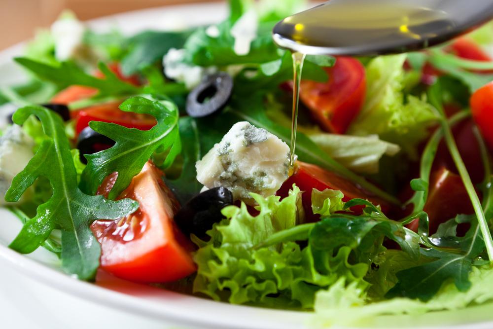 Ensalada mediterránea con aceitunas negras, queso y tomates muy rojos, rociada por aceite de oliva con una cuchara