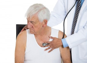 Elderly caucasian man in a white t-shirt with a physician listening to his chest with a stethoscope