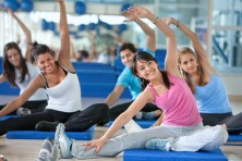 Several women exercising on floor mats