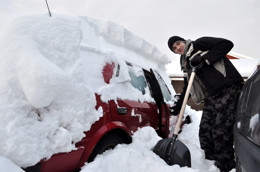 Man shoveling snow from around a red car