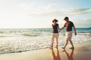 Man and woman couple walking on beach holding hands