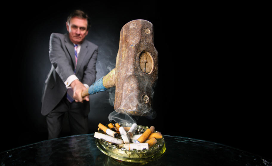 Dr. Hurt with hammer fighting tobacco and hitting cigarettes (cropped image)