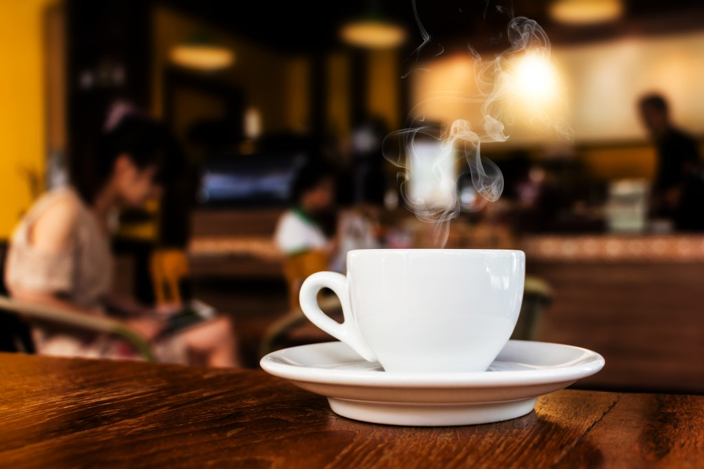 Cup of steaming coffee or tea on table