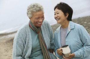 two women laughing together and sharing friendship - diversity
