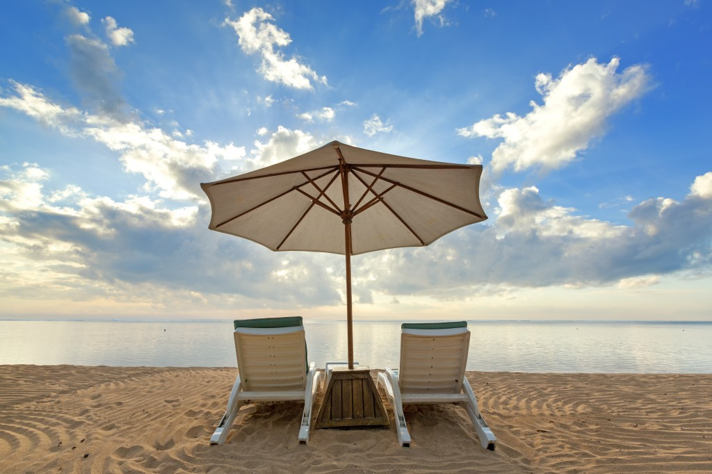 Summer vacation beach scene with chairs and umbrella