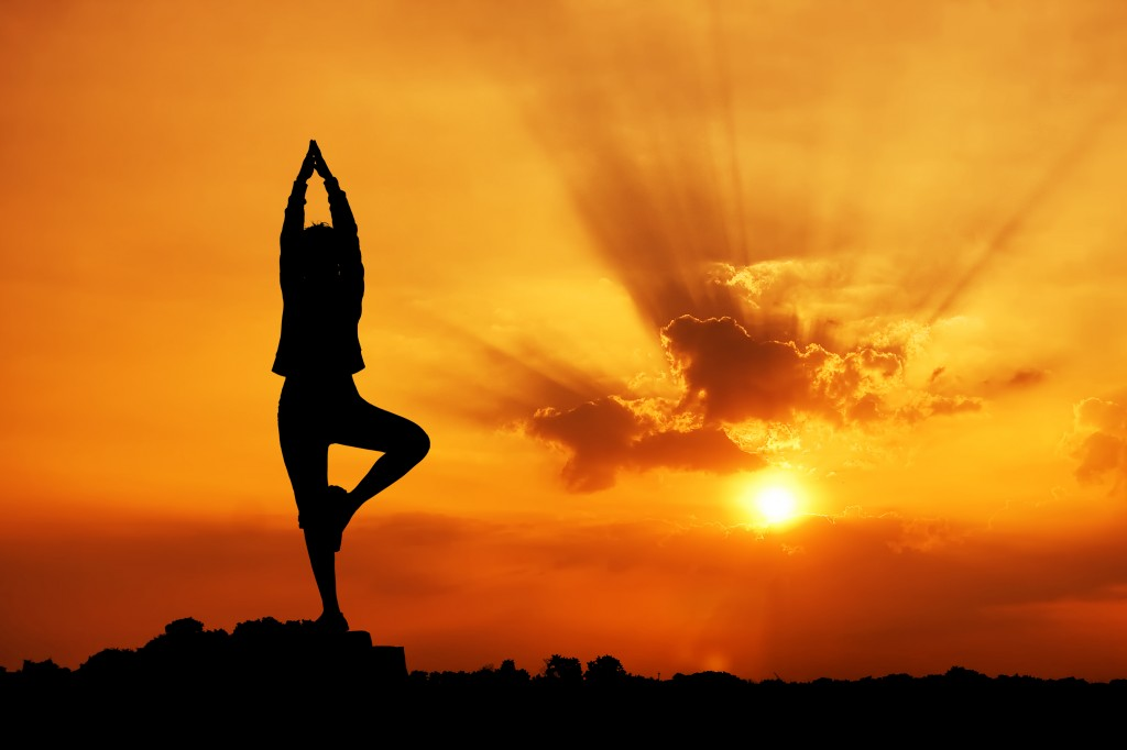 Women's health - Silhouette of a Yoga woman in the morning sunrise