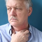 Man holding his sore throat - maybe suffering from GERD, acid reflux, heartburn