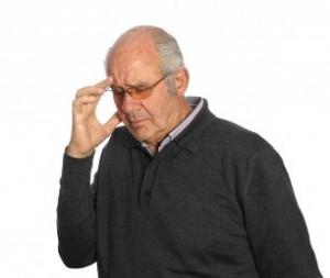 Hombre de edad que se toca la frente y parece encontrarse mareado o con dolor de cabeza