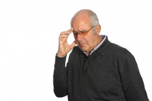 elderly man touching forehead and appears to be dizzy or has a headache