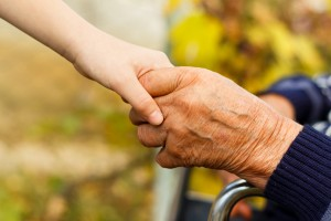 close up of child's hand holding an older adult hand with kindness
