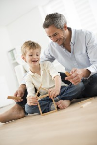 adult man playing building blocks game with child