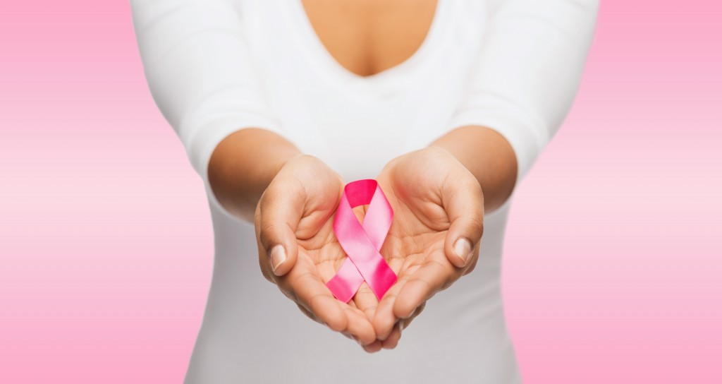 woman's hands holding pink breast cancer survivor ribbon
