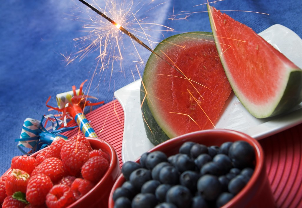 July 4th celebration picnic table with watermelon, berries and sparkler