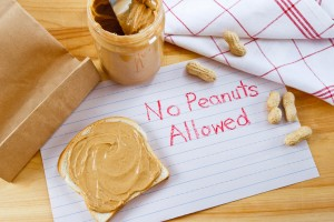 food allergies sign that says 'no peanuts' next to peanut butter jar