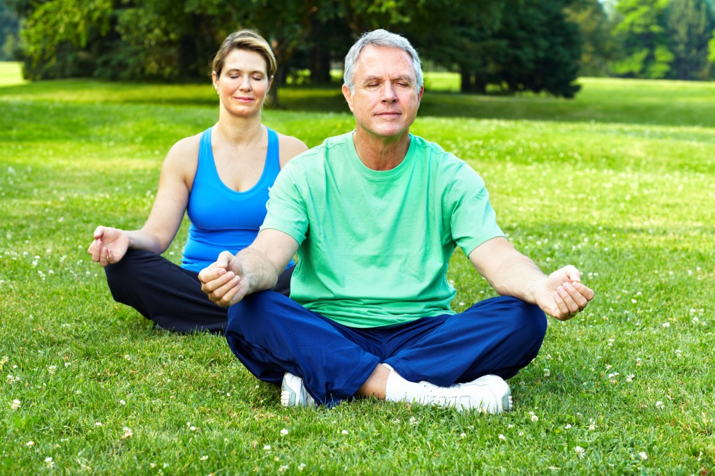 middle-aged couple doing yoga outside on a grassy lawn