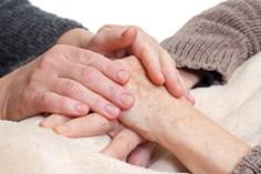 La persona que cuida del paciente le sostiene las manos