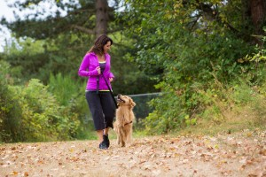 woman exercising outdooors and walking her dog