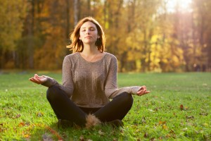 woman meditating outside in nature - alternative medicine