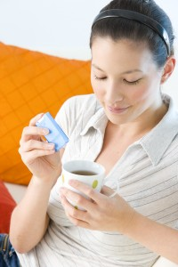 woman putting sugar substitute or artificial sweetener in coffee cup