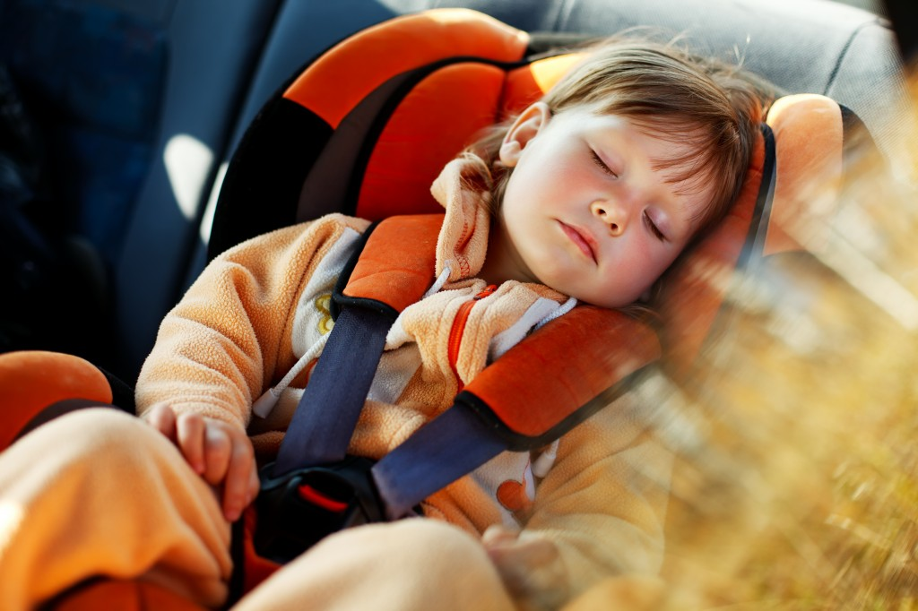 young child in car seat sleeping in car