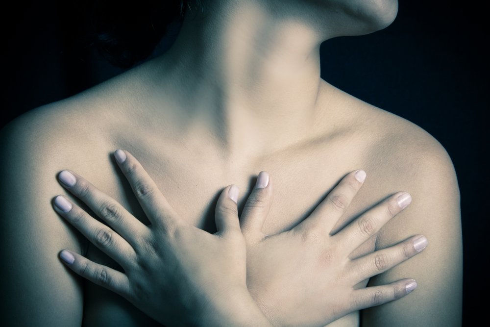 woman covering breasts with hands