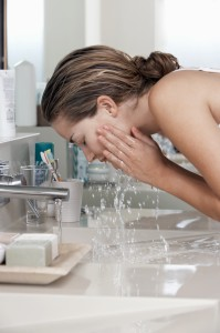 young woman with healthy sking washing face at bathroom sink
