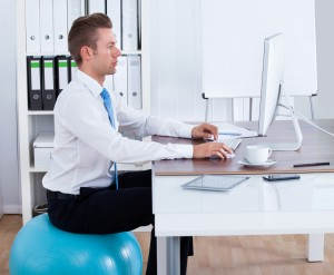 man sitting at work desk on a fitness exercise ball