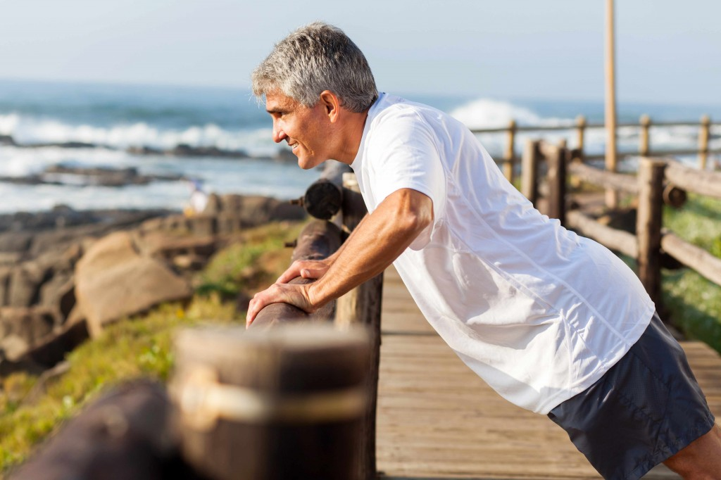 middle-aged man exercising and stretching near ocean